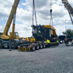Two cranes loading a huge machine on a drop deck